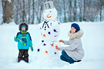 Mother and her little son painting a snowman