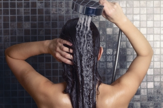 Young Woman Washing Her Long Hair Under The Shower